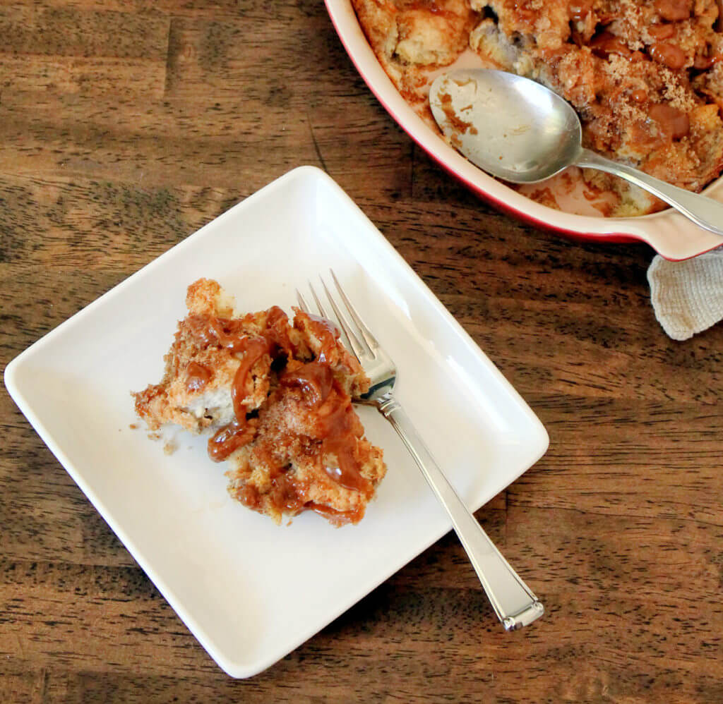Overhead view of a serving of old fashioned bread pudding with caramel sauce on a white square plate.