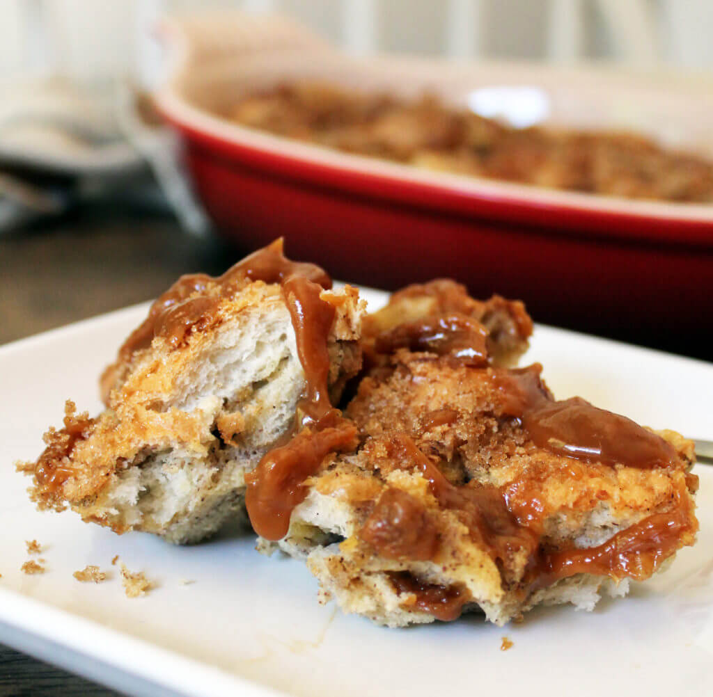 Closeup of a serving of old fashioned bread pudding with caramel sauce on a white square plate.