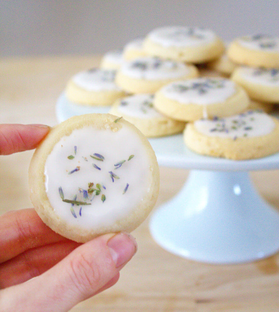 A hand holds up a decorated shortbread cookie. A plate stacked with decorated cookies is in the background.
