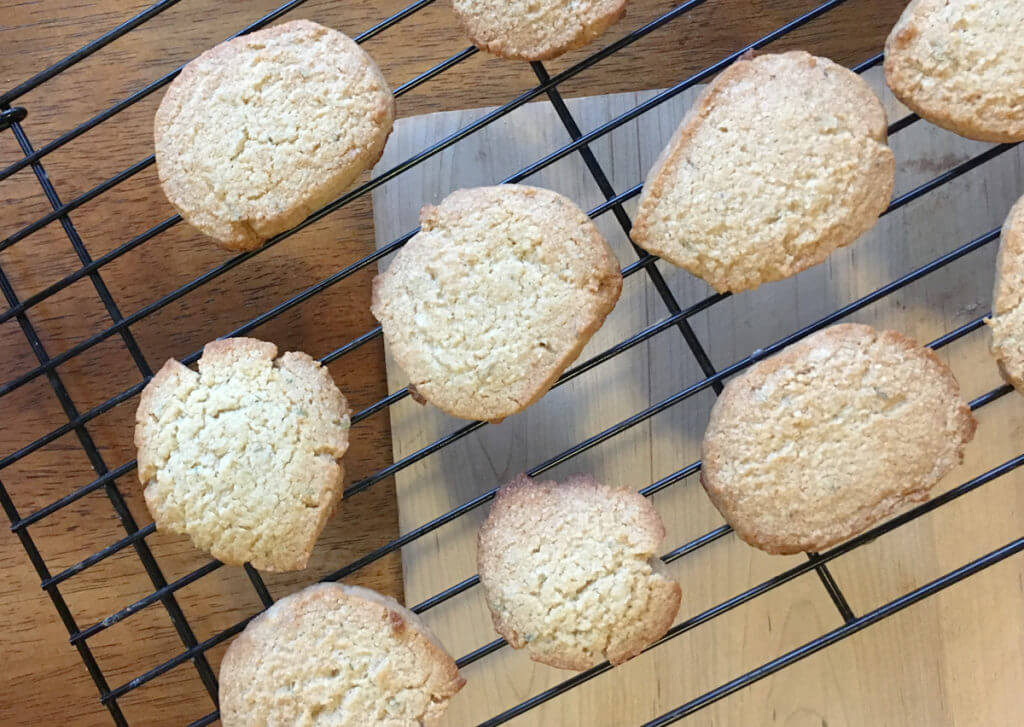 Overhead view of baked rosemary honey shortbread cookies cooling on a wire rack.