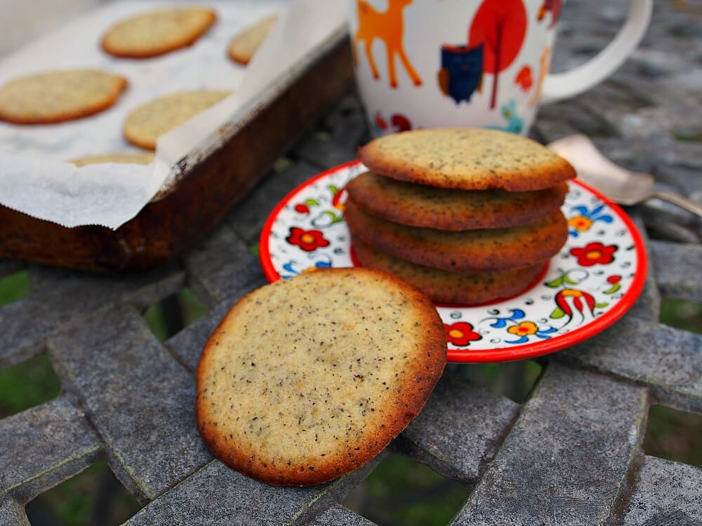 A stack of Earl Grey butter cookies sit on a red and white floral plate alongside a fall-themed mug of tea and a tray of baked cookies.
