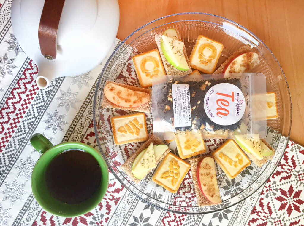 Overhead view of a Christmas tea party with loose leaf tea, cookies, and tea sandwiches on a clear glass plate with a white teapot and green mug.