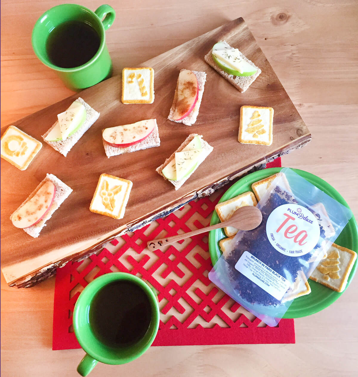 Overhead view of a Christmas tea party with loose leaf tea, cookies, and tea sandwiches on a wooden board and green plates and mugs.
