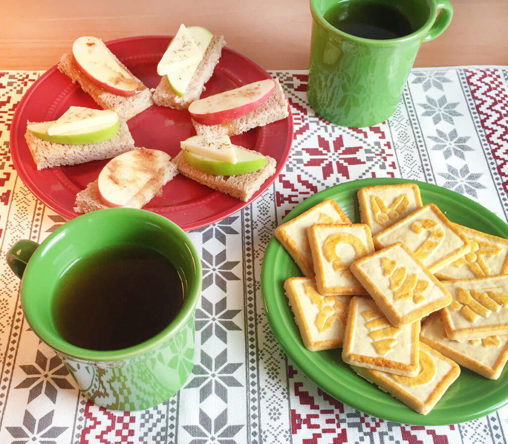 Overhead view of a Christmas tea party with cookies and tea sandwiches on red and green plates with tea in green mugs.
