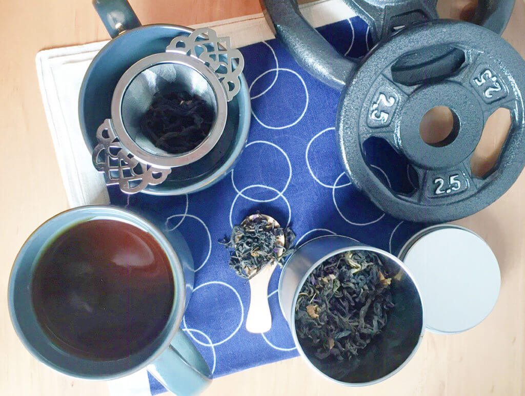 Overhead view of loose leaf tea, tea infusers, mugs of brewed tea, and weights on a blue and white tea towel.
