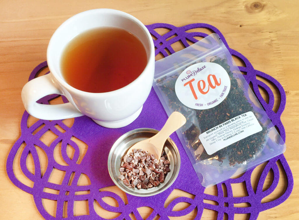 A white teacup filled with tea sits on a purple placemat with a bag of loose leaf tea and a scoop of cacao nibs.
