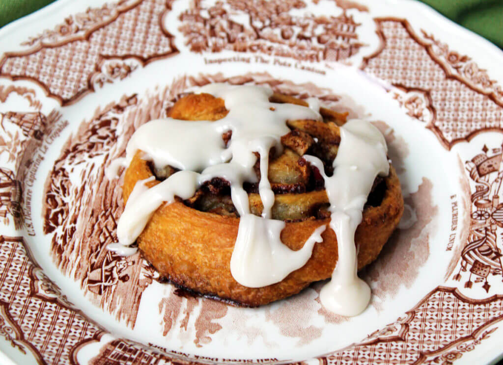 A cinnamon roll with apples and vanilla drizzle icing sits on a brown and white vintage plate.