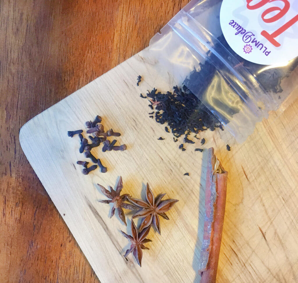 Overhead view of a bag of loose leaf black tea on a wooden board, surrounded by cinnamon sticks, star anise, and cloves.