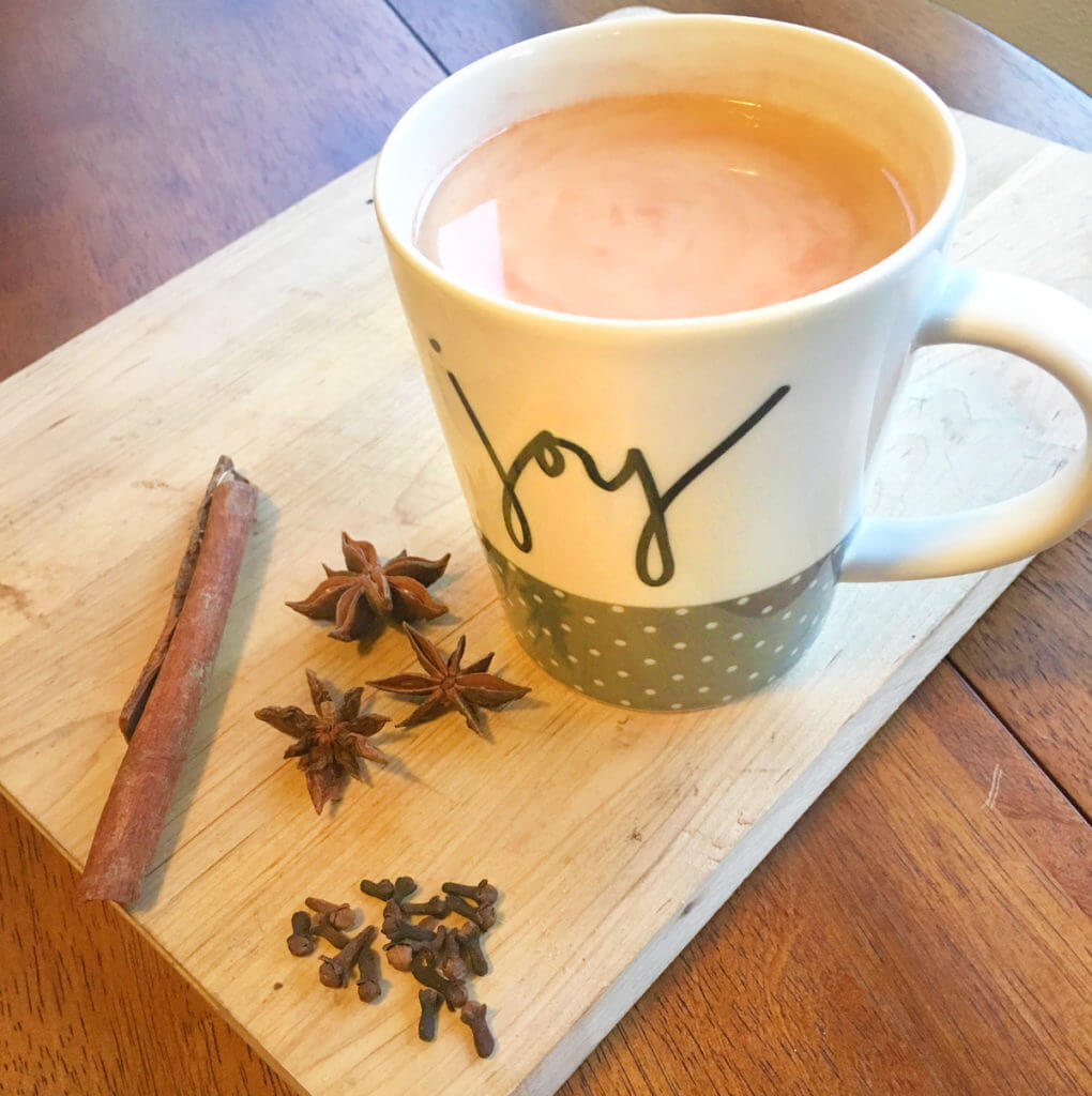 "A mug that says ""joy"" and is filled with chai tea sits on a wooden board, surrounded by cinnamon sticks, star anise, and cloves."