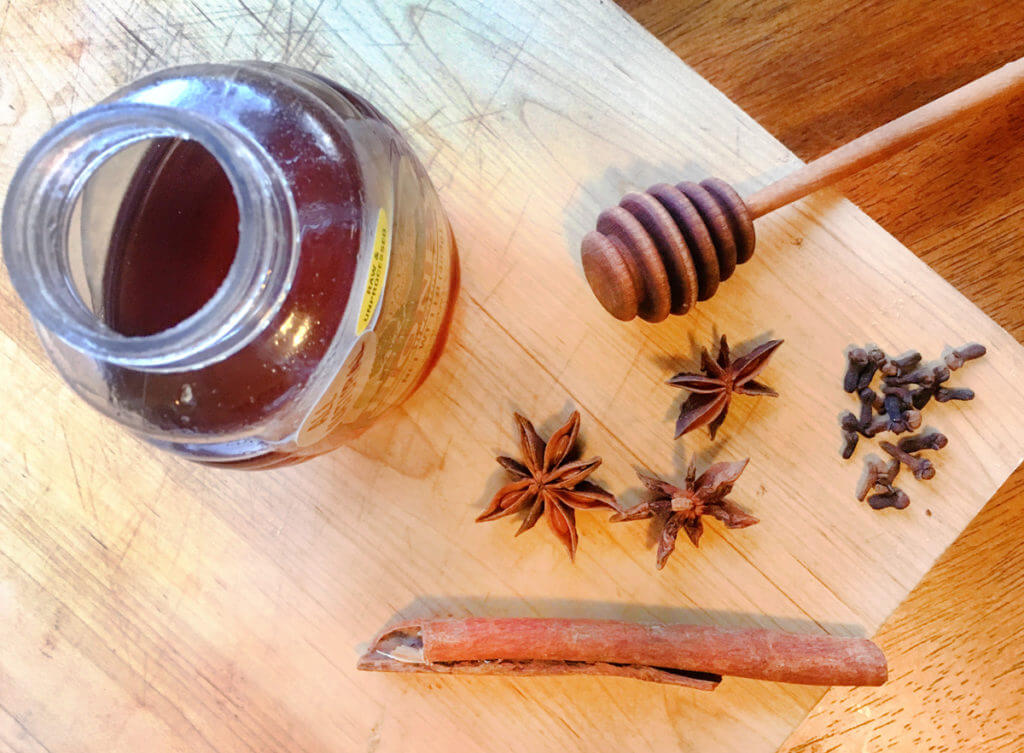 Overhead view of a jar of honey on a wooden board, surrounded by cinnamon sticks, star anise, and cloves.