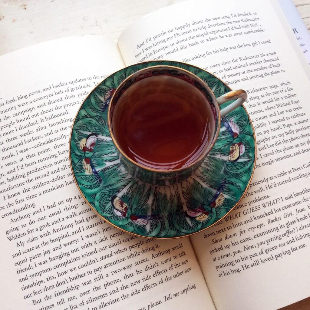 A green floral teacup sits on top of an open book.