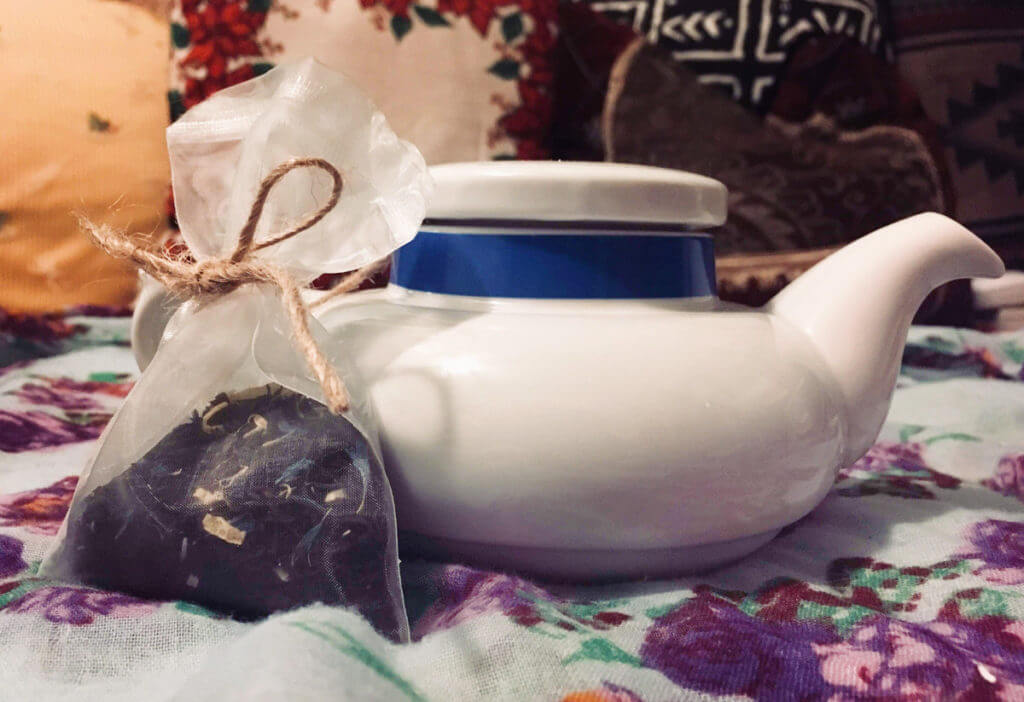 A silk sachet of tea sits next to a white and blue teapot.