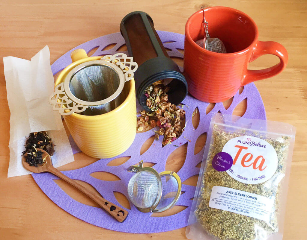 Several brightly colored mugs, tea infusers, and bags of loose leaf tea are arranged on a purple placemat.