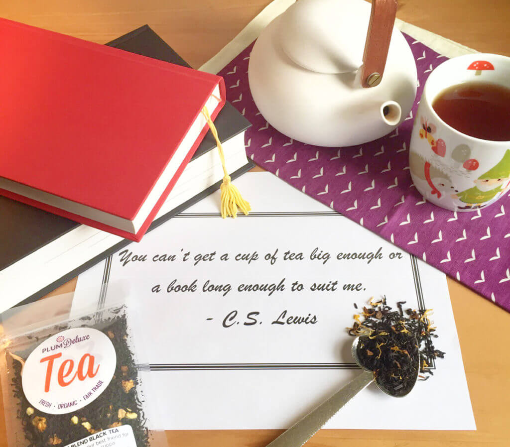 Overhead view of a tea saying by C.S. Lewis surrounded by a teaspoon of loose leaf tea, a teapot, and books.