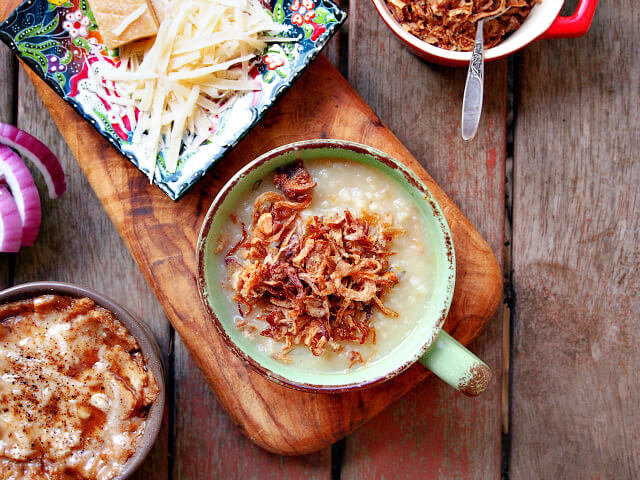 A large mug of dill potato soup topped with fried onions rests on a wooden board along with grated cheese.