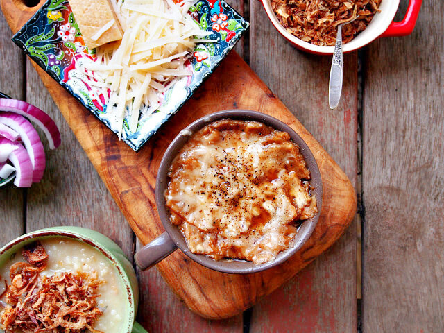 A large mug of gingery red onion soup rests on a wooden board along with a plate of shredded cheese.