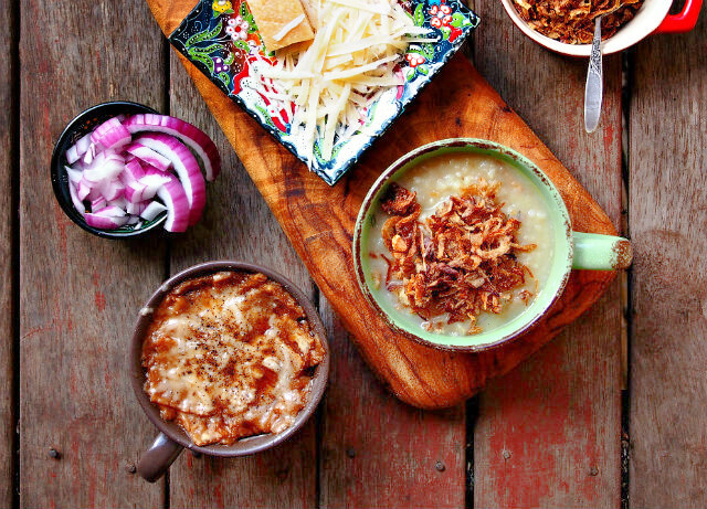 Mugs full of soup and fried onions are arranged on a wooden table along with a plate of grated cheese and fresh onions.