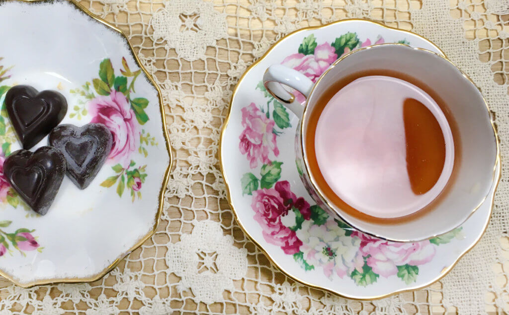 Overhead view of a cup of tea on a floral saucer next to a dish of heart shaped chocolates.