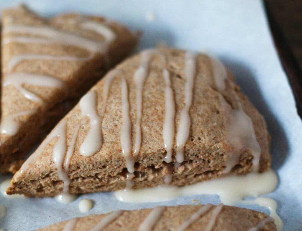 Closeup of vegan banana oat scones on a parchment-lined baking tray.