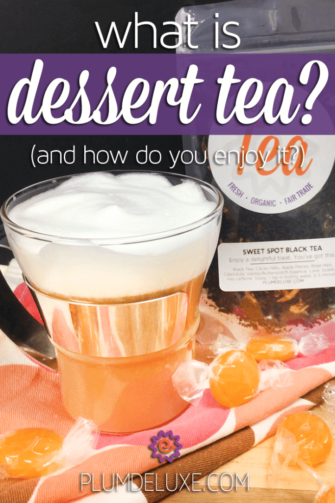 A dessert tea latte sits on an orange and pink polka dot tea towel surrounded by candies.