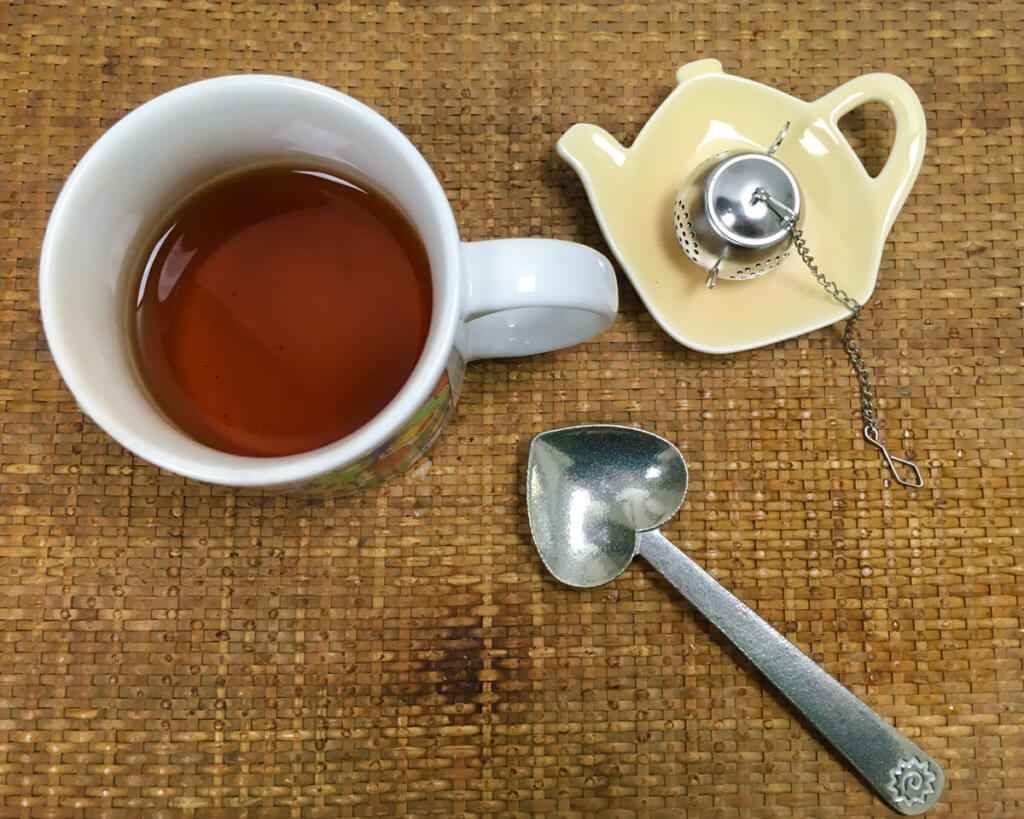 Overhead view of a mug of tea, a heart-shaped pewter tea scoop, and a metal teapot-shaped infuser on a teapot-shaped ceramic tea rest, all arranged on a woven tray.