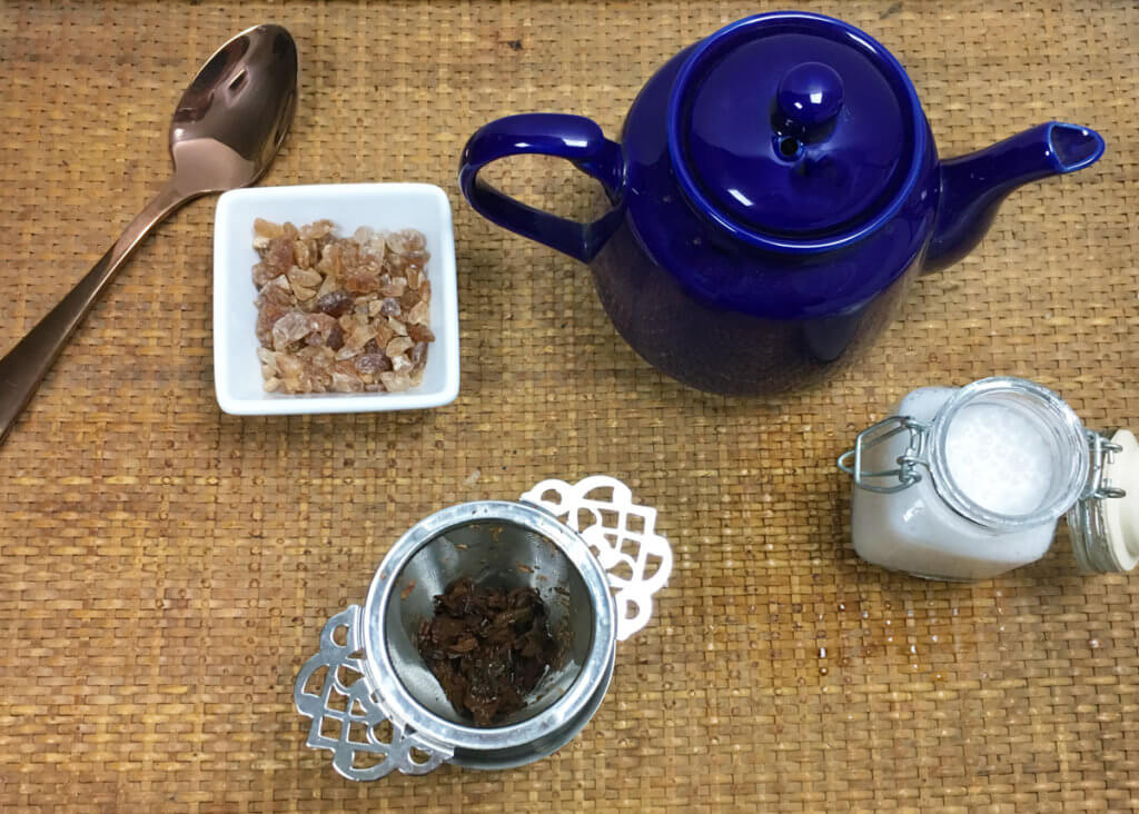 Overhead view of a dark blue teapot, square bowl of sugar, rose gold teaspoon, and victorian infuser full of loose leaf tea arranged on a woven tray.