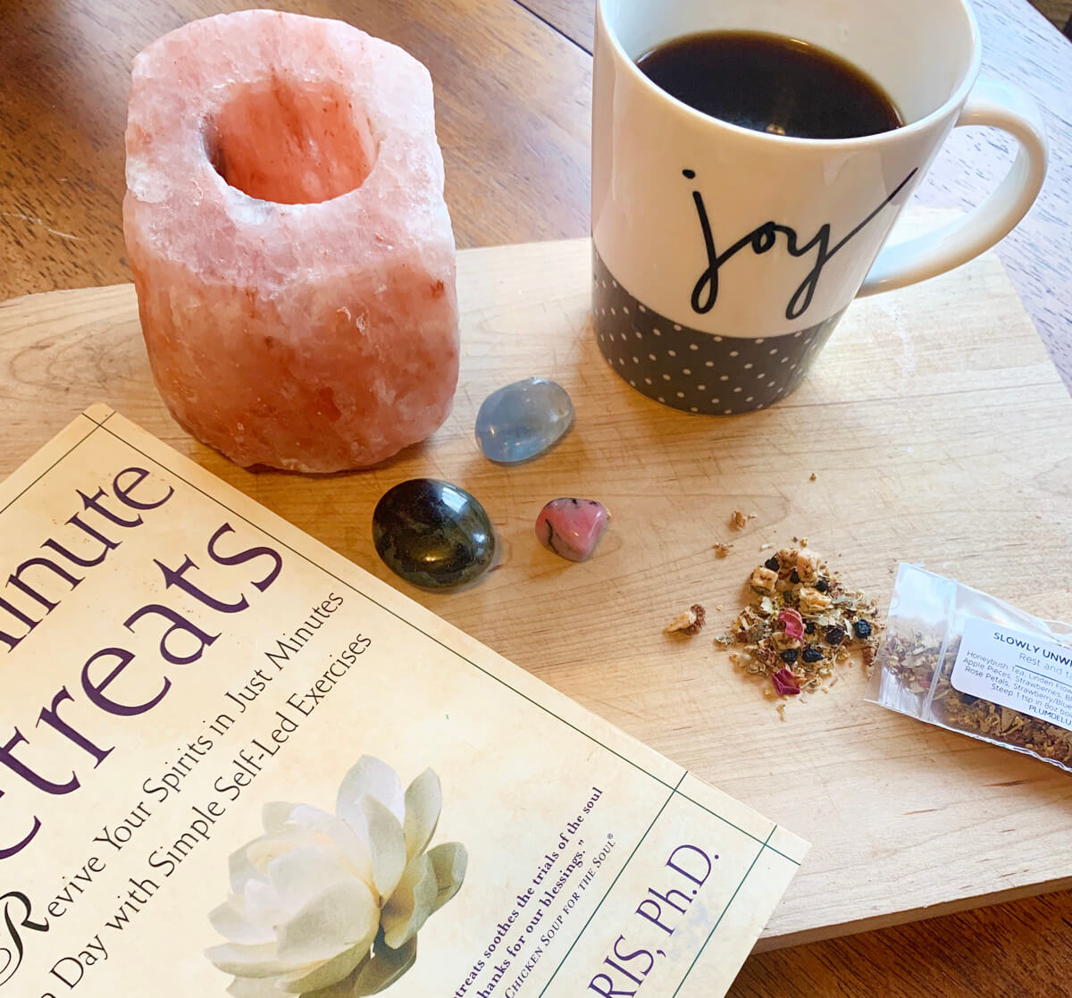 A cup of tea, Himalayan sea salt candle holder, several polished crystal stones, a bag of a loose leaf herbal tea, and a book sit on a wooden surface.