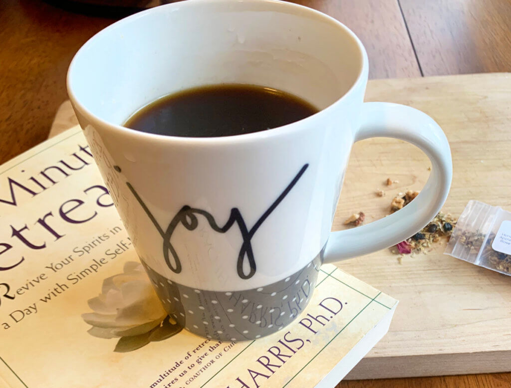 "A mug of tea with the word ""joy"" written on it rests on top of a book."
