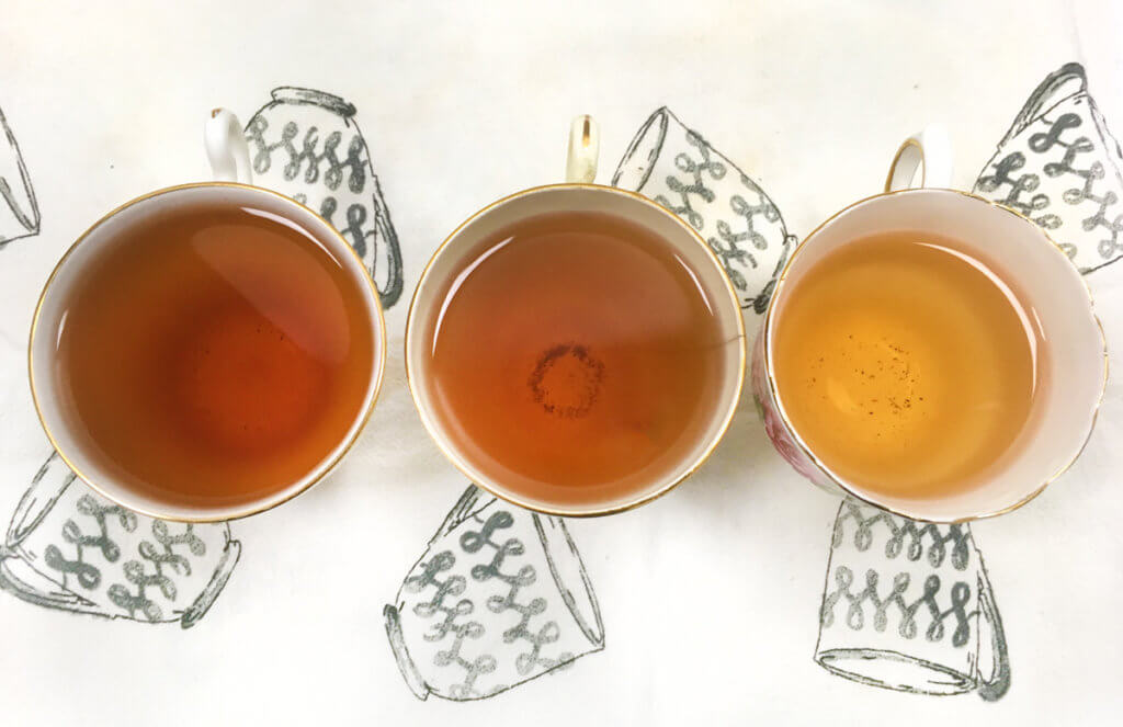 Overhead view of three teacups with different shades of tea, on a white and gray teacup print tea towel.