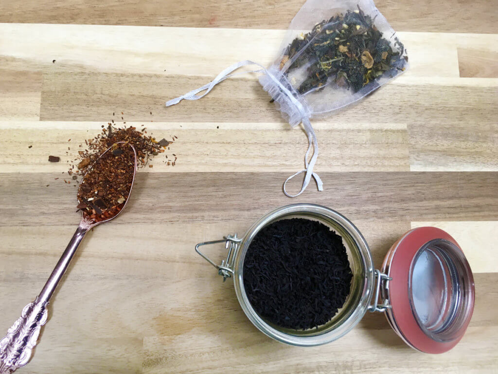 Three different kinds of loose leaf tea – black tea, white, tea, and herbal tea – are arranged on a wooden table.