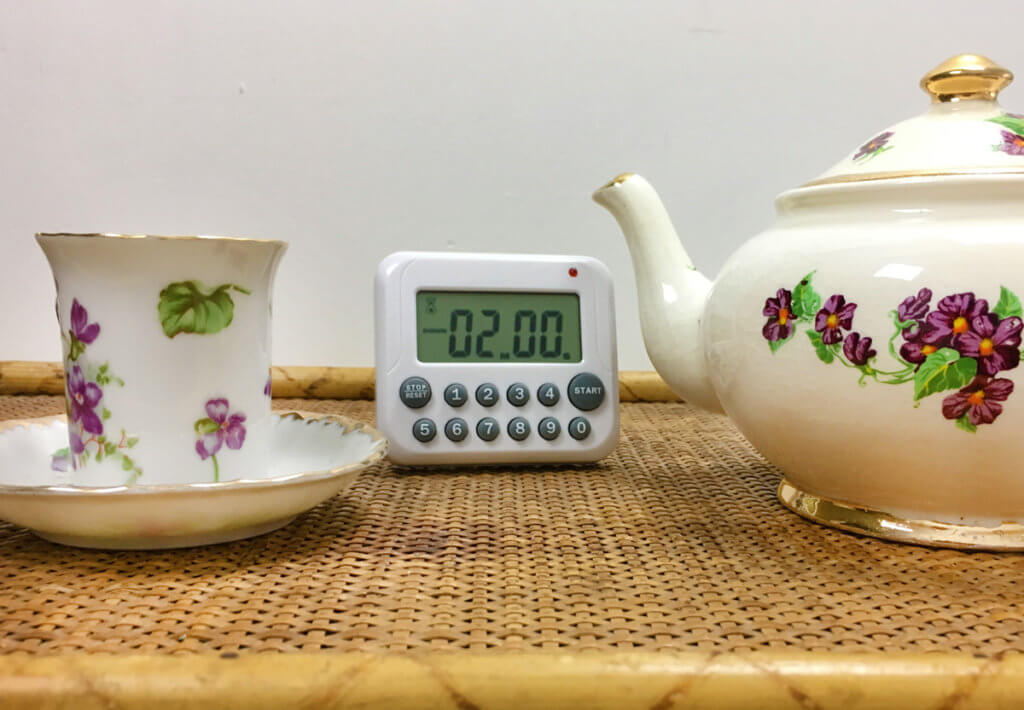 A digital timer is flanked by a white violet teacup and matching teapot on a woven tray.