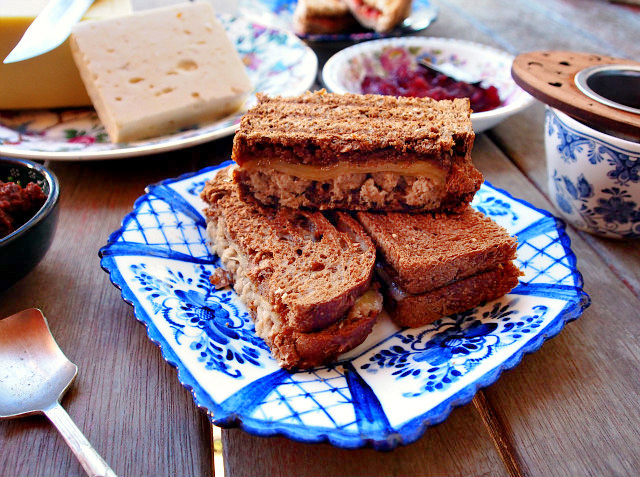 A grilled cheese sandwich with pork rillette, caramelized onion, and chutney on rye sits on a blue and white plate.