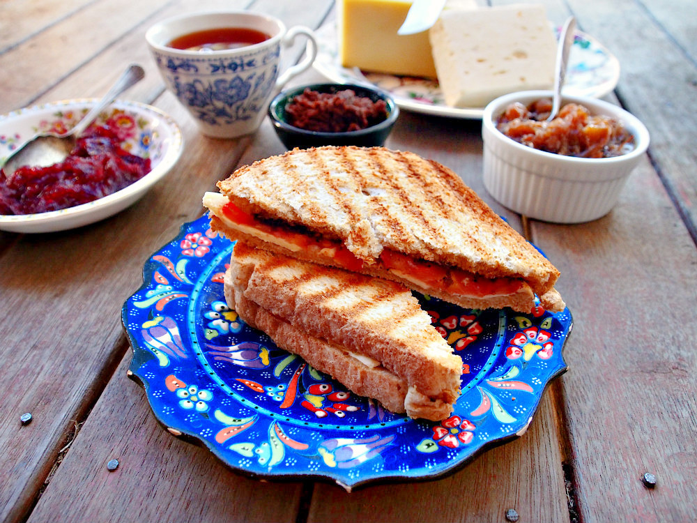 A grilled cheese with feta, tomatoes, and black olive tapenade sits on a blue floral plate.