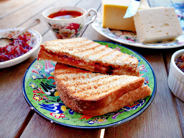 A grilled cheese with parmesan and cranberry port sauce on wheat sits on a green and blue floral plate.