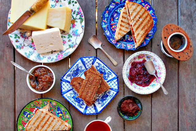 Overhead view of a wooden table filled with plates of fancy grilled cheese sandwiches, cheeses, and spreads.