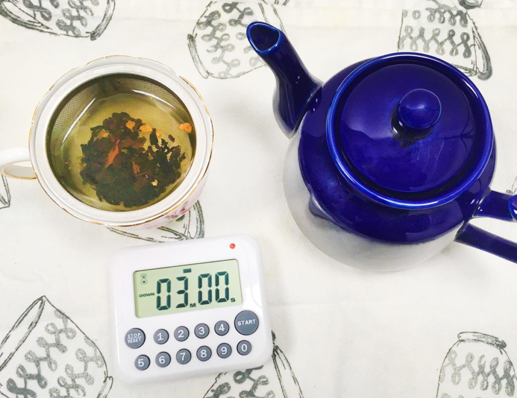 Overhead view of a dark blue teapot, teacup infusing loose leaf tea, and a digital timer on a teacup print tea towel.