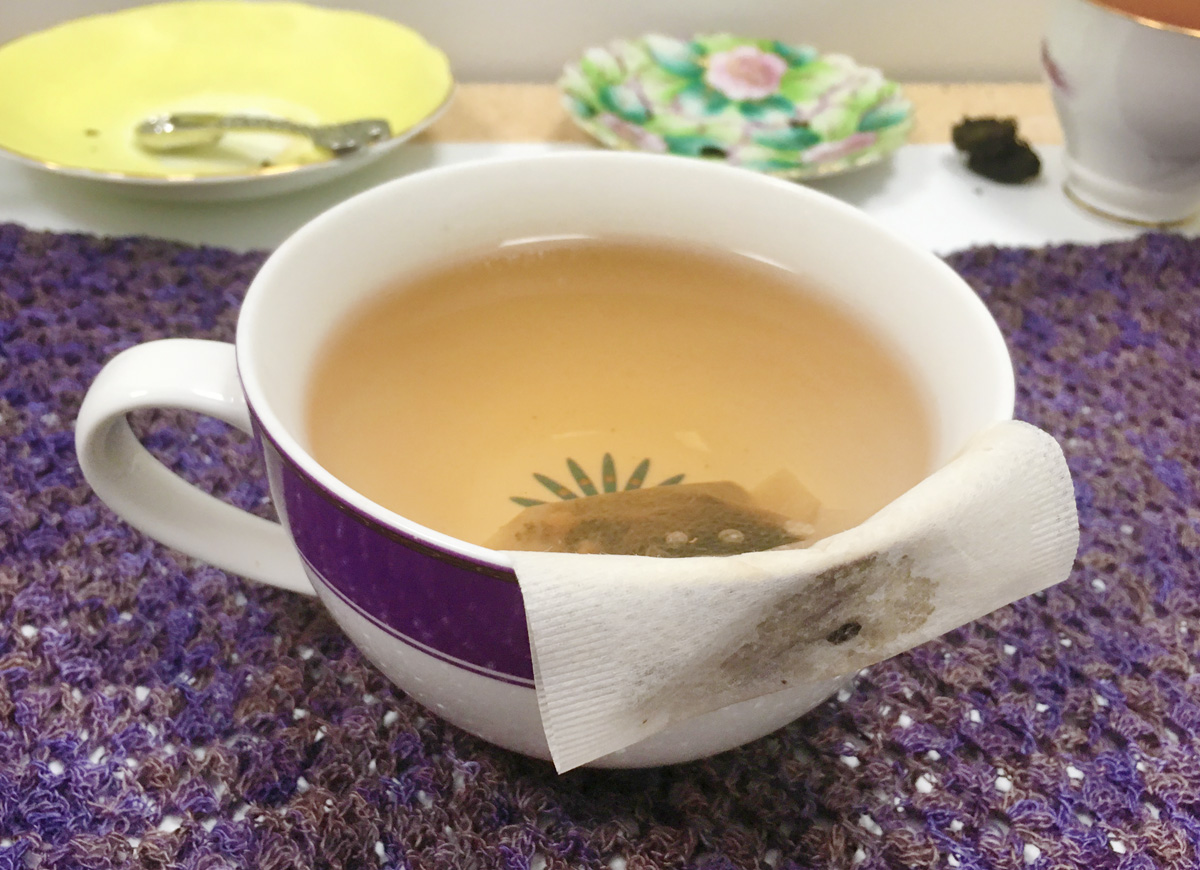 A large white and purple mug holds a paper filter bag for steeping tea.