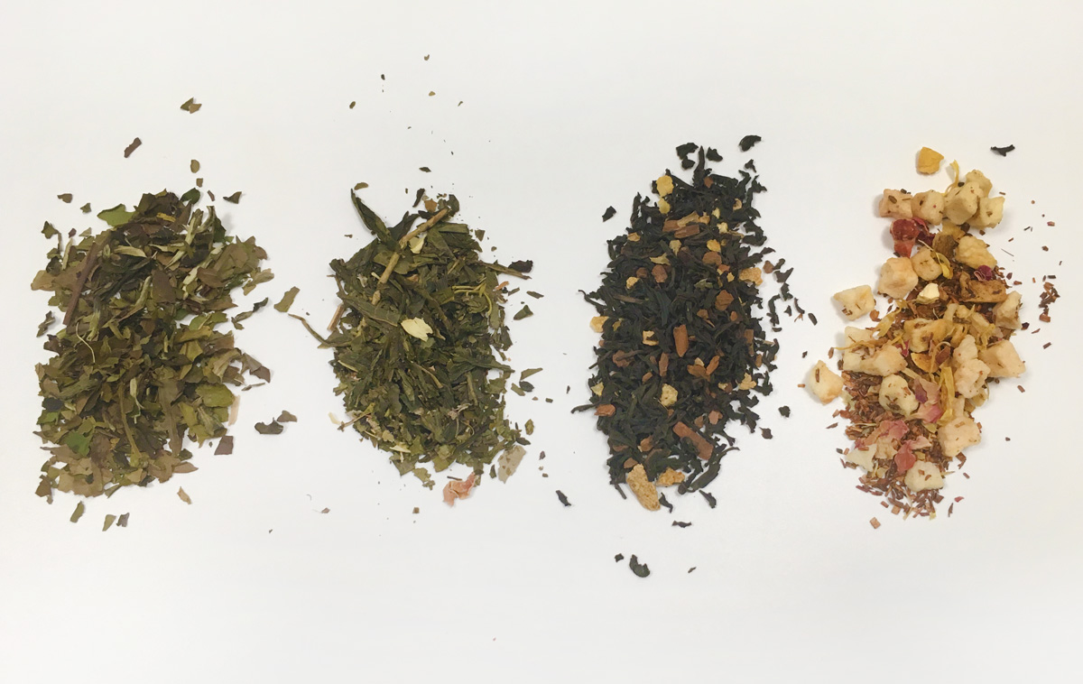 Four kinds of loose leaf tea are lined up in a row on a white background.