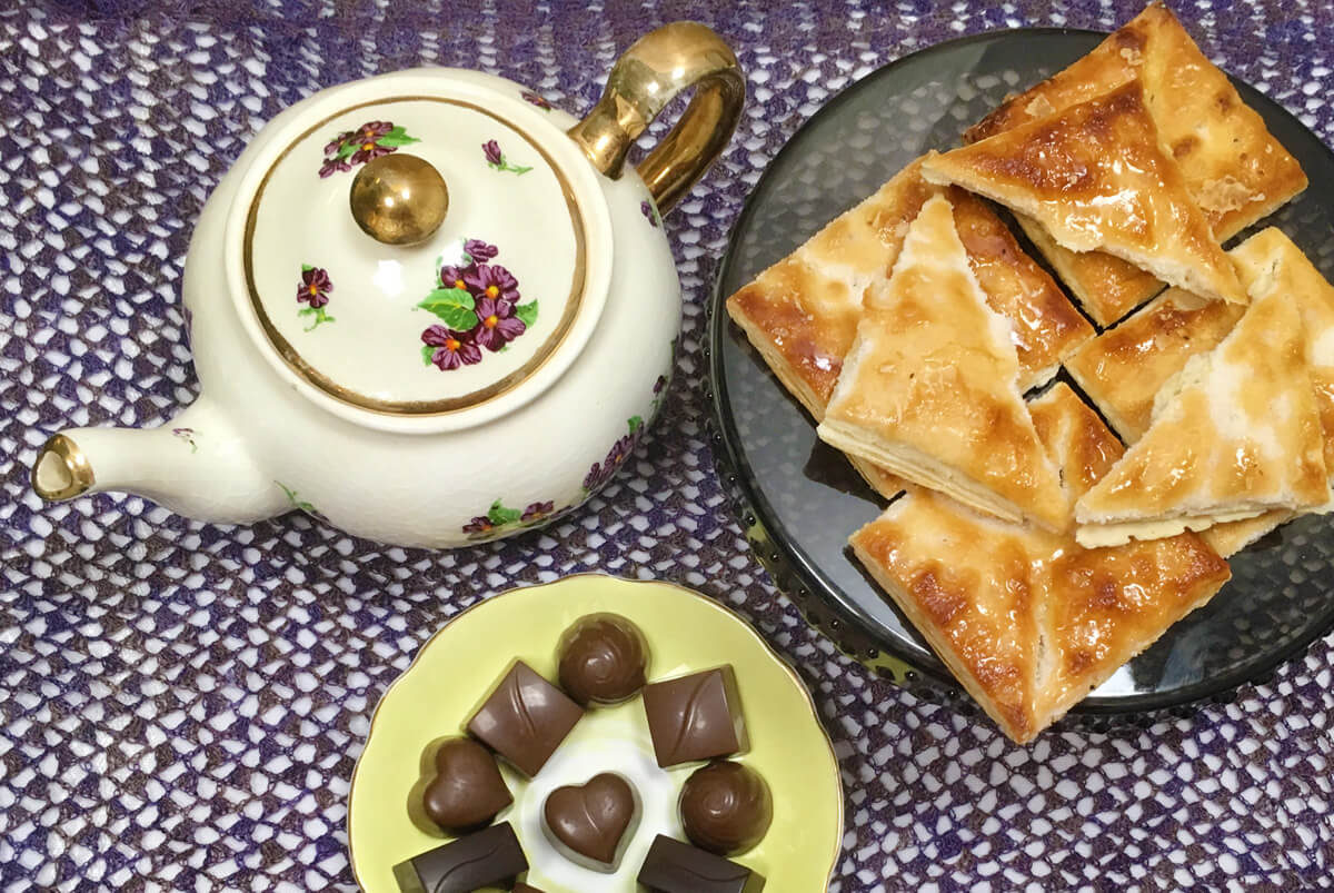 Overhead view of a white and purple violet teapot, yellow plate of chocolates, and pile of pastries on a dark purple lace cloth.