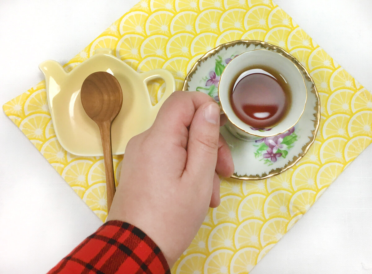 Overhead view of a hand reaching for a white and purple violet teacup and a wooden teaspoon on a yellow teapot-shaped tea rest, all arranged on a lemon print yellow napkin.