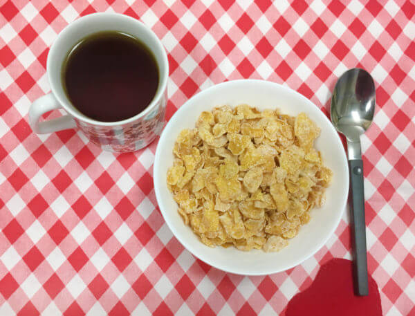 Overhead view of a bowl of cereal, spoon, and mug of breakfast blend tea on a red and white checkered tablecloth.