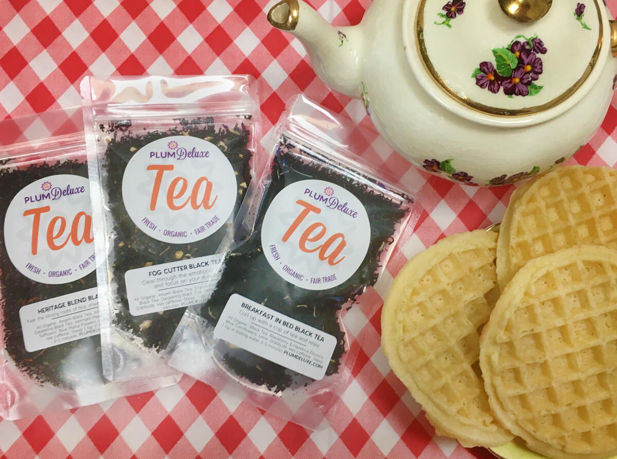 Overhead view of three bags of loose leaf breakfast blend tea next to a plate of waffles and a white floral teapot on a red and white checkered tablecloth.