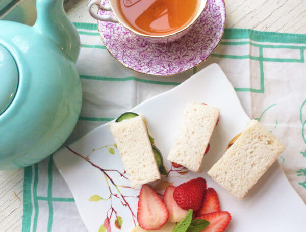 Overhead view of a plate of fruit and tea sandwiches surrounded by a robin's egg blue teapot and a purple and white floral teacup full of tea on a vintage white and green cloth.