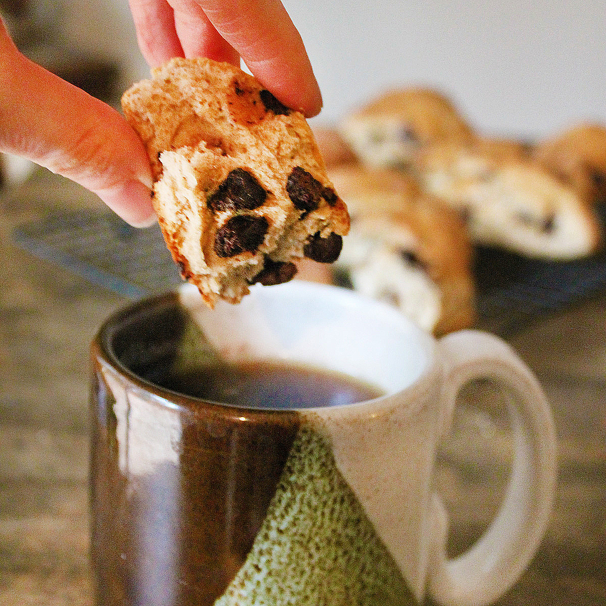 A hand dunks a bite of a chai chocolate chip scone into an earthenware mug of tea.