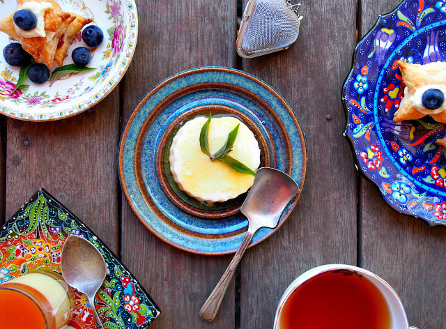 A mini cheesecake with passionfruit topping sits on a blue plate surrounded by other mini desserts for a tea party.