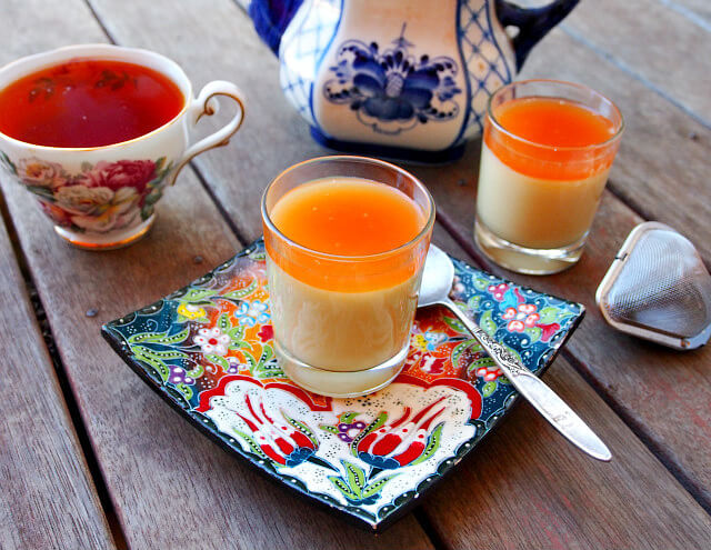 A mini panna cotta with caramel sauce is in a clear shot glass on a floral plate, with a teapot and cup of tea in the background.