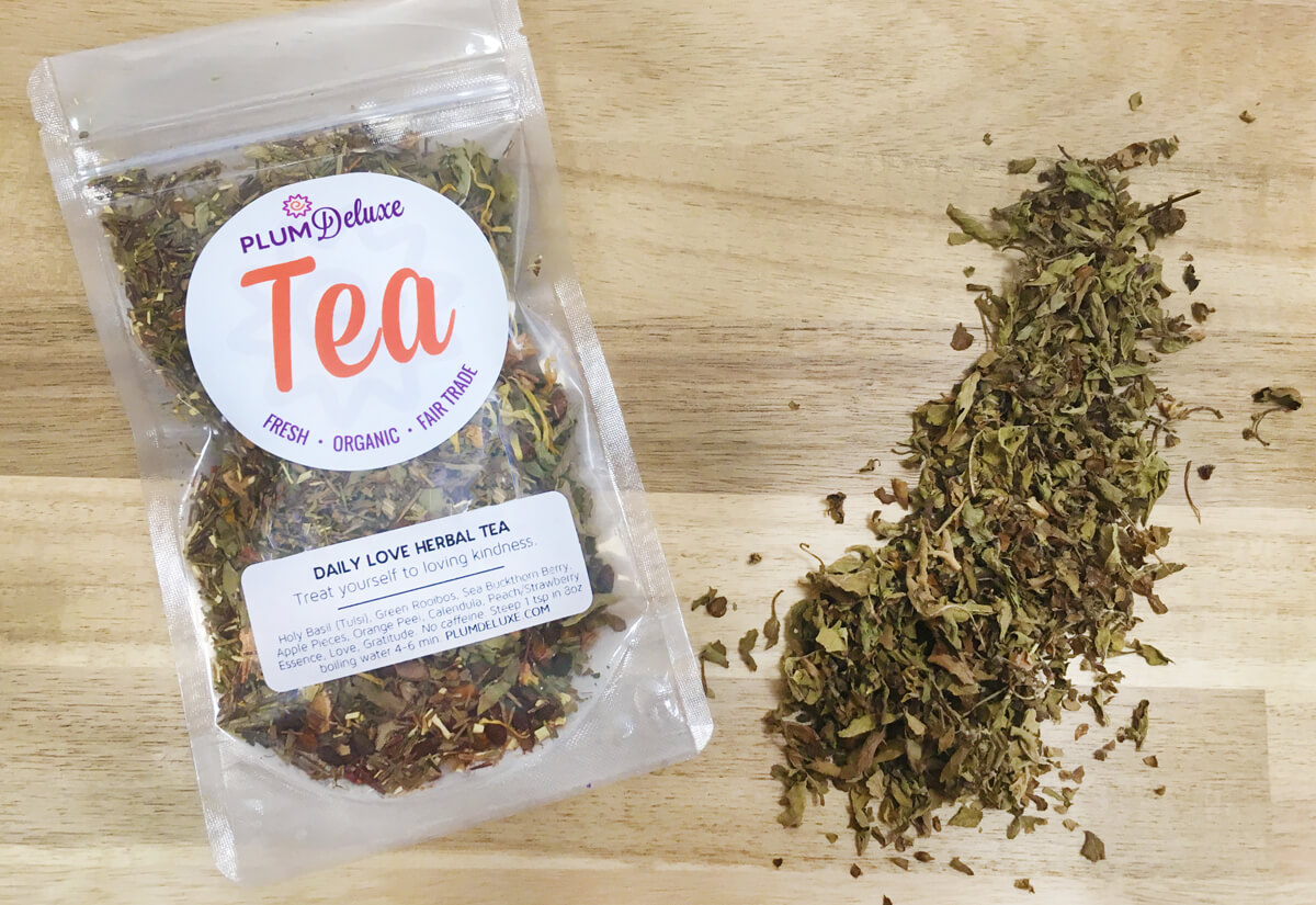 A bag of Plum Deluxe Daily Love tulsi loose leaf tea sits on a wooden table.