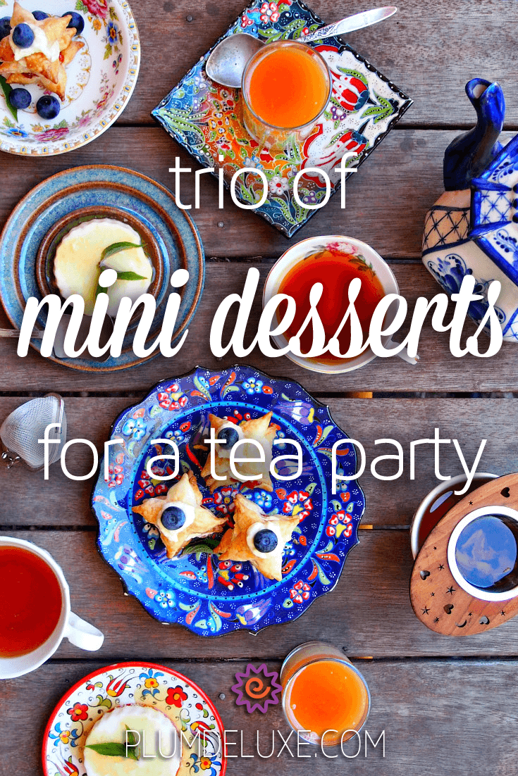Overhead view of three mini desserts for a tea party spread out on a wooden table with a teapot and cups of tea.
