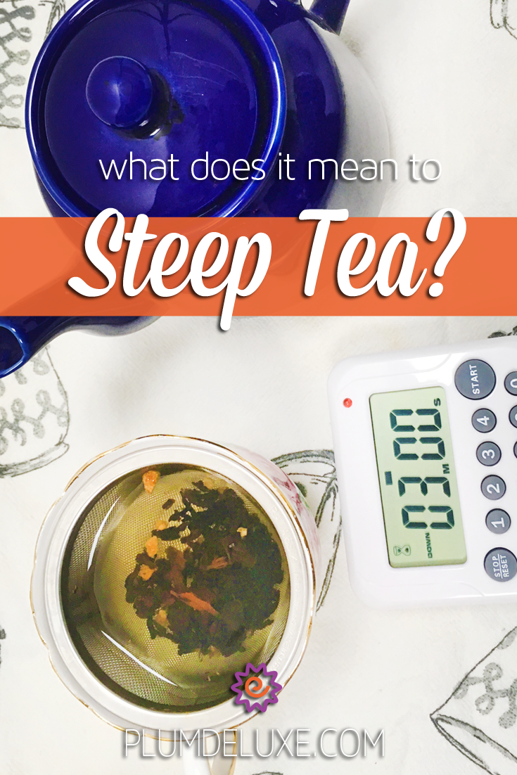 Overhead view of a dark blue teapot, teacup infusing loose leaf tea, and a digital timer on a teacup print tea towel with the words: what does it mean to steep tea?