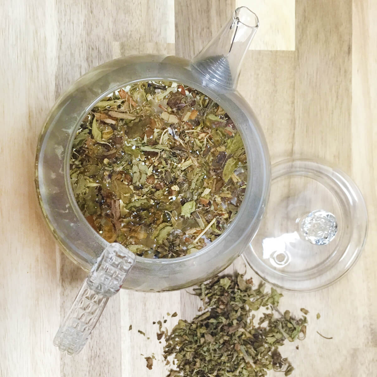 Overhead view of a glass teapot full of holy basil tea.